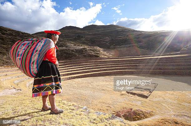 woman in traditional costume at moray archaeological site. cusco. peru - hugh sitton stock pictures, royalty-free photos & images