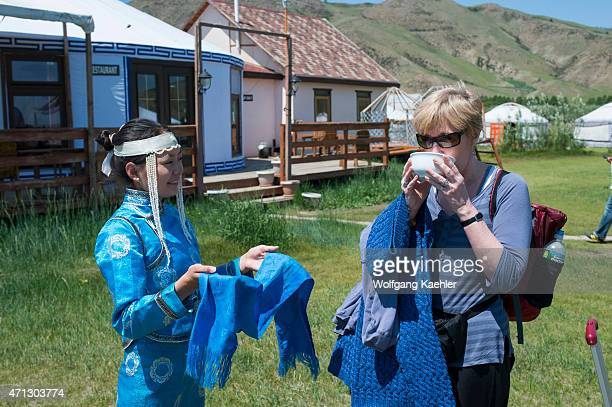 Woman in traditional costume welcoming tourist with milk at Munkh Tenger ger camp in Kharakhorum Mongolia