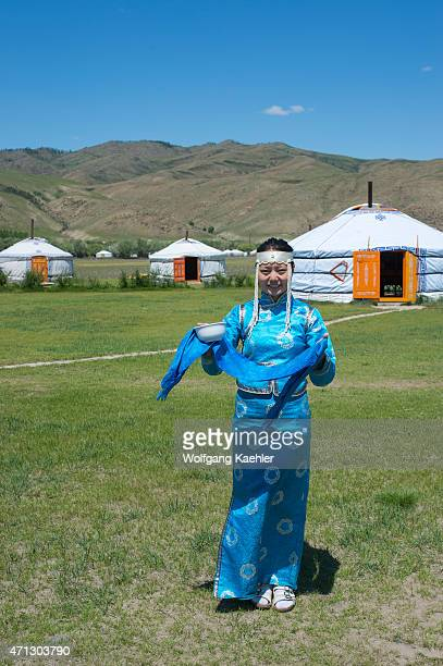 Woman in traditional costume welcoming tourist with milk at Munkh Tenger ger camp in Kharakhorum, Mongolia.