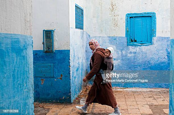 CONTENT] Woman in traditional djellaba carrying her baby on back and walking on the blue streets of Larache medina Morocco 2013