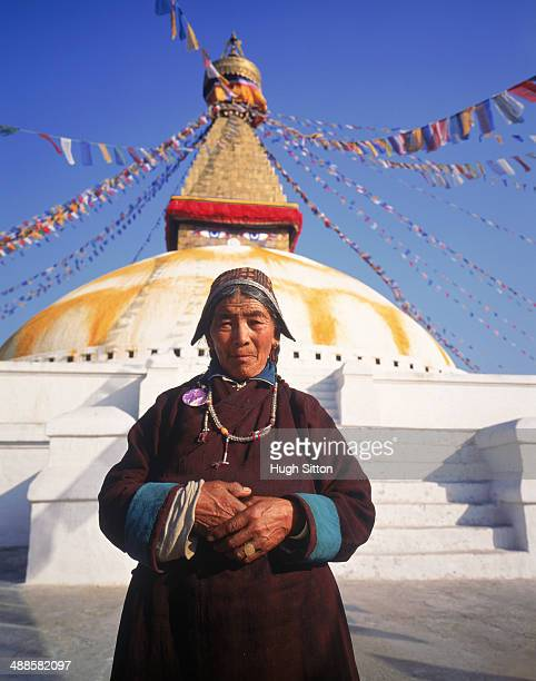 woman in traditional dress at baudhanath stupa - hugh sitton stockfoto's en -beelden