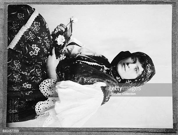 A woman in traditional dress poses for a threequarter length portrait Prague Czech Lands ca 19191924