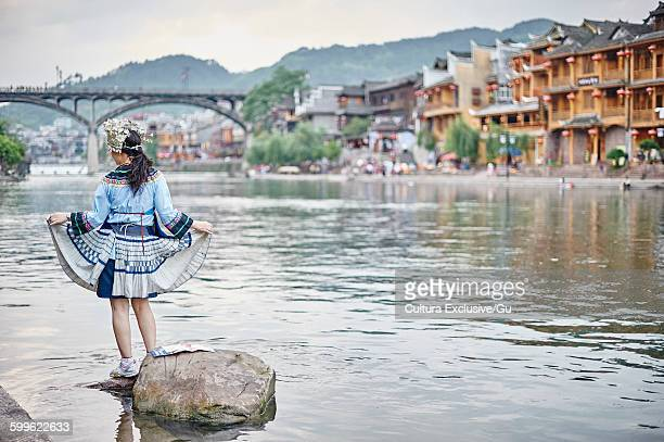 Woman in traditional dress standing on rock in river, rear view, Fenghuang, Hunan, China