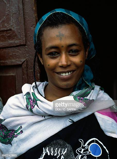 Woman in traditional dress with symbols on her face Dessie Ethiopia