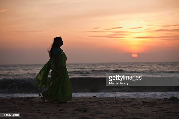 woman (28 years old) in traditional green sari walking on marari beach alappuzha, kerala, india - 25 29 years stock pictures, royalty-free photos & images