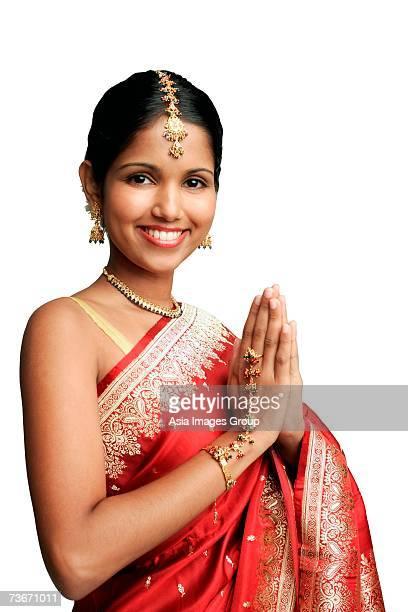 woman in traditional indian costume, smiling at camera - prayer pose greeting bildbanksfoton och bilder