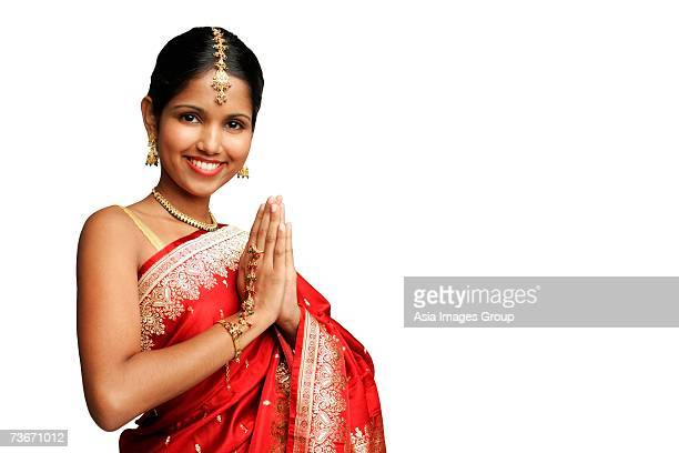 woman in traditional indian costume standing against white background, smiling at camera - prayer pose greeting bildbanksfoton och bilder
