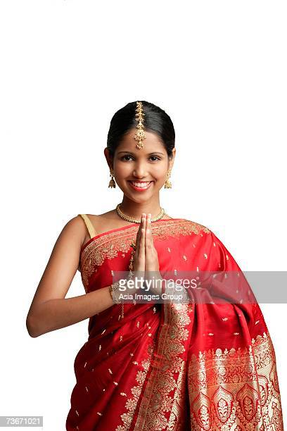 woman in traditional indian costume, standing with hands together, smiling at camera - prayer pose greeting bildbanksfoton och bilder