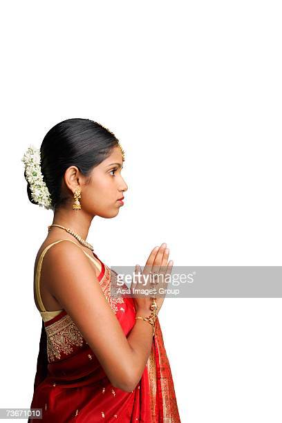 woman in traditional indian costume, standing with hands together, side view - prayer pose greeting bildbanksfoton och bilder
