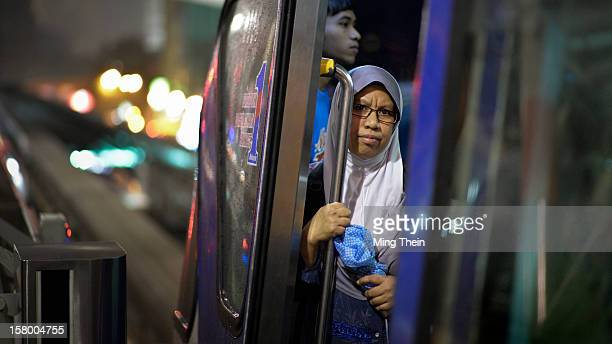 A woman in traditional Malay tudung looks out from the door of the LRT waiting for it to depart in the evening from a station in downtown Kuala...