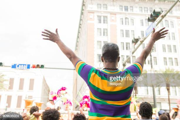 woman in traditional mardi gras colors raises arms for parade - mardi gras parade stock photos and pictures