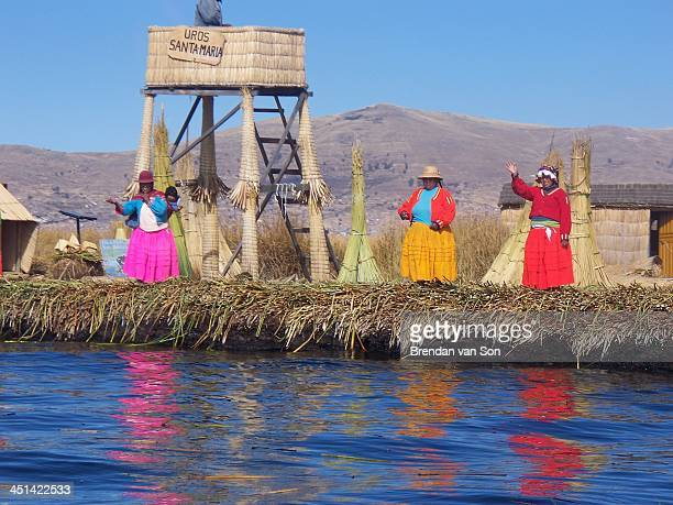 Woman in traditional outfits waving on the reed islands of Lake Titicaca, Peru