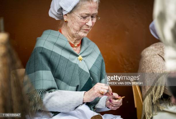 Woman in traditional Scheveningen costume repairs a fishing net during the 72nd edition of Vlaggetjesdag marking the official start of the herring...