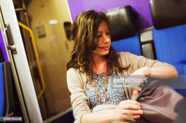 woman in train checking her watch - mid adult women photos et images de collection