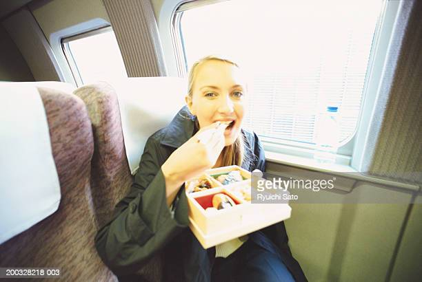 Woman in train eating lunch with chopsticks, portrait
