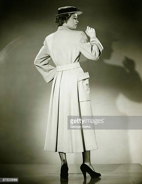Woman in trench coat and hat posing in studio (Rear view), (B&W)