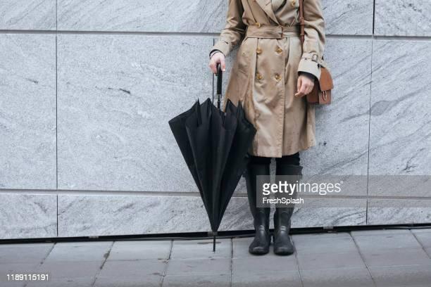 eine frau im trenchcoat halten regenschirm - gummistiefel frau stock-fotos und bilder
