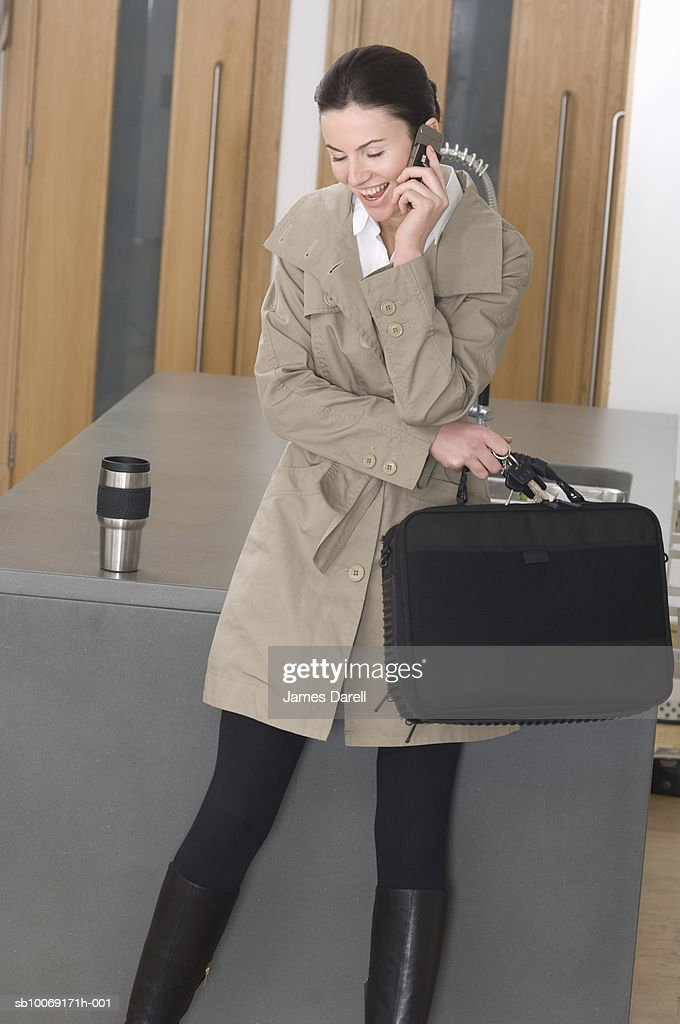 Woman in trench coat using mobile phone in lobby : Stockfoto