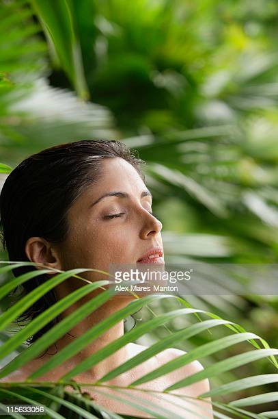 Woman in tropical garden, eyes closed