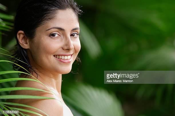 Woman in tropical garden, smiling