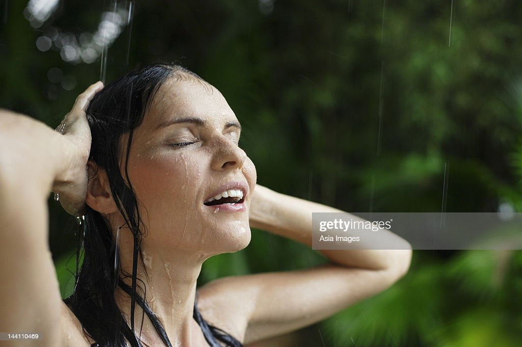 woman in tropical rain shower  hands on head Stock Photo Woman In Tropical Rain Shower Hands On Head Getty Images