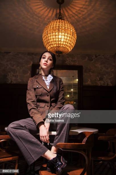 woman in trouser suit sitting on table - pant suit stock pictures, royalty-free photos & images