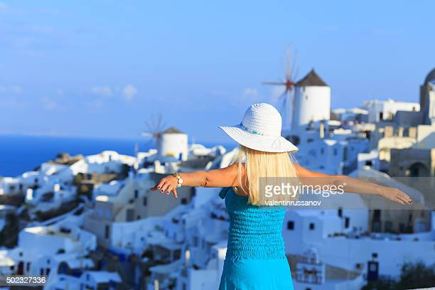 Woman in turqoise dress with hands up at Santorini