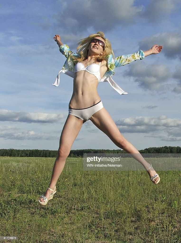 Woman in underclothes, jumps on the field : Stock Photo
