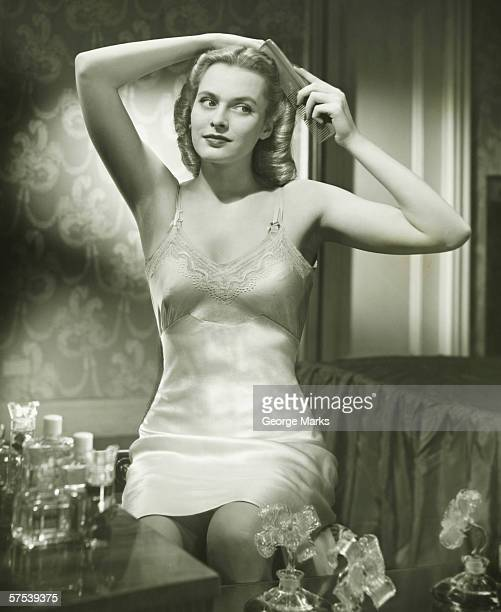 Woman in underskirt brushing hair in bedroom, (B&W), portrait