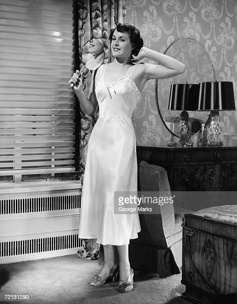 woman in underskirt standing in bedroom (b&w) - women in slips stock photos and pictures
