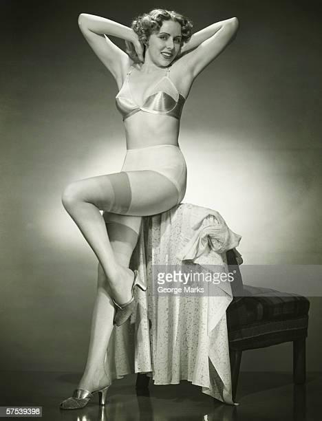 Woman in underwear and stockings posing in studio, (B&W), portrait