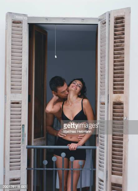 Woman in underwear being kissed by man on balcony