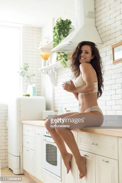 a mulher no roupa interior está sentando-se na cozinha - mulher sensual - fotografias e filmes do acervo