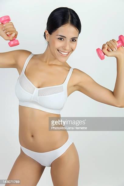 Woman in underwear lifting dumbbells