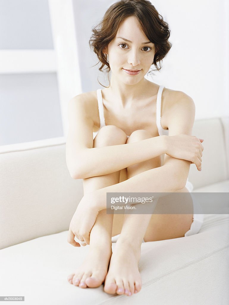 Woman in Underwear Sitting on a Sofa : Stock Photo