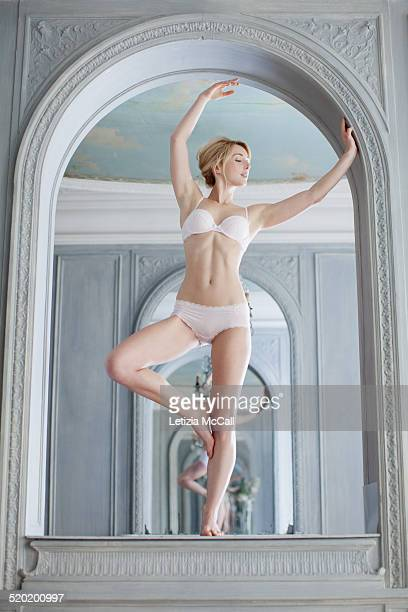 Woman in underwear standing on alcove like dancer