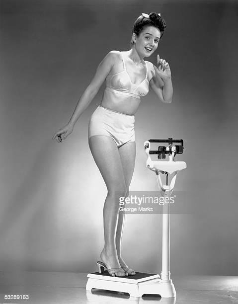 woman in underwear standing on scale - sostén fotografías e imágenes de stock