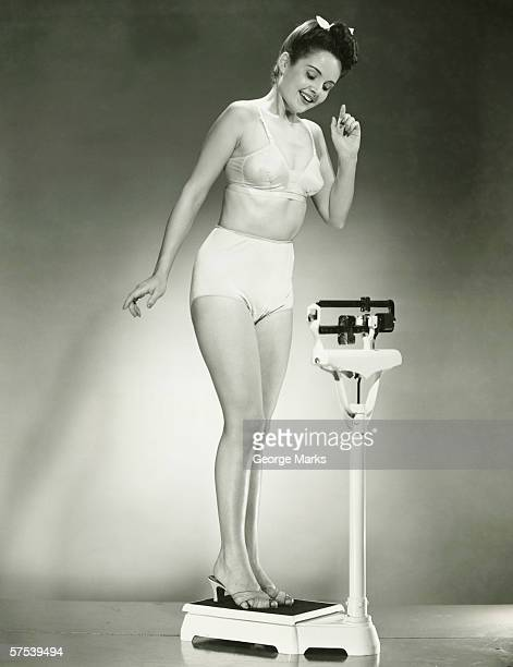 Woman in underwear standing on scale, (B&W)