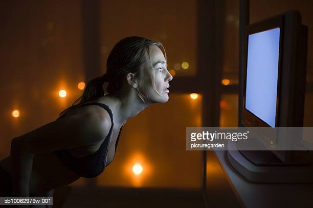 Woman in underwear staring at TV at night, side view