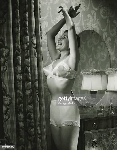 Woman in underwear stretching in bedroom, (B&W)