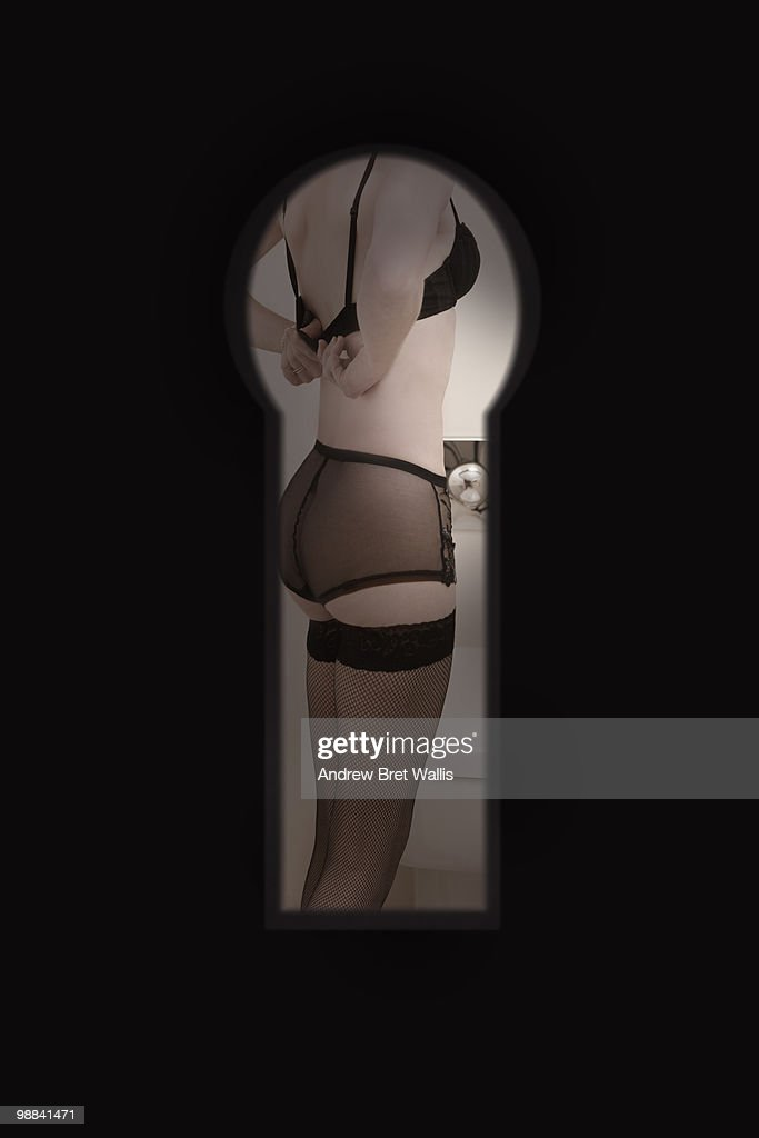 woman in underwear undressing, through keyhole : Stock Photo