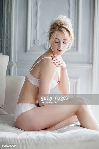 Woman in underwear with her hand on shoulder