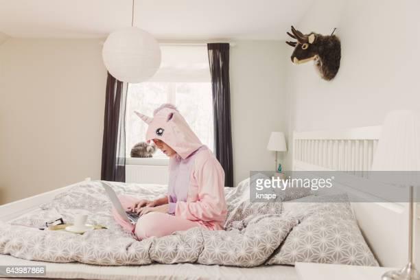 Vrouw in unicorn kostuum in slaapkamer