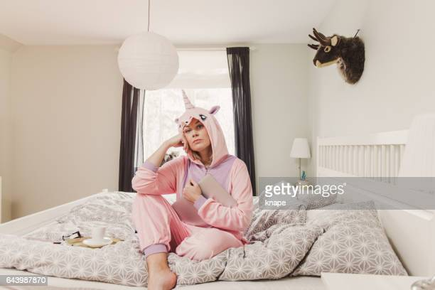 Woman in unicorn costume in bedroom