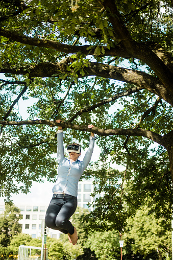 Woman in urban park hanging at branch of a tree wearing VR glasses - gettyimageskorea