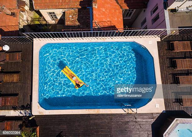 Woman in vacations relaxing on air mattress in swimming pool