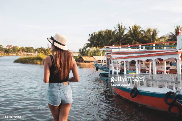 woman in vacations standing along the river in hoi an ancient town in vietnam during a sunny day . - pretty vietnamese women stock pictures, royalty-free photos & images