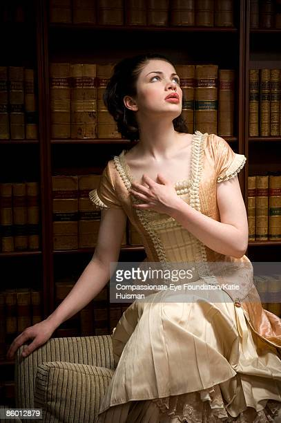 woman in victorian dress in a library - victorian style stock pictures, royalty-free photos & images