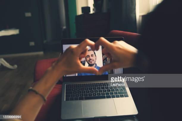 femme dans l'appel vidéo avec son partenaire - relations sociales à covid19 temps de distanciation sociale - rendez vous amoureux photos et images de collection