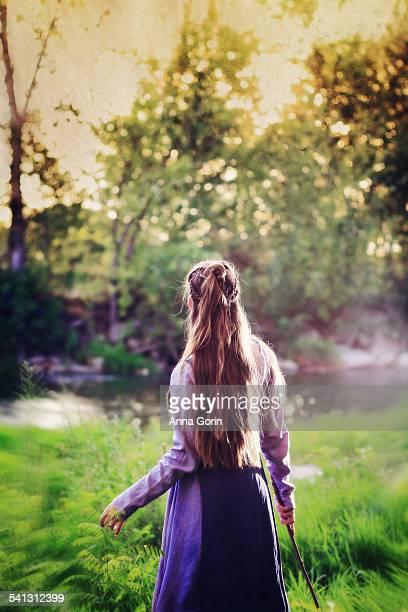 Woman in viking dress turns toward river, textured